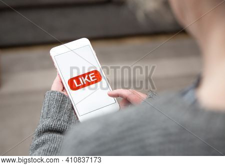 A Woman Tapping A Like Icon On The Touchscreen Of Her Mobile Phone In A Social Media Concept