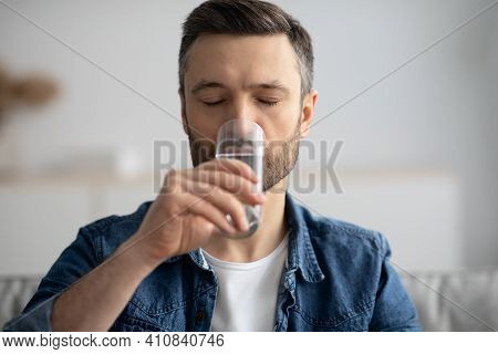 Closeup Of Middle-aged Man With Eyes Closed Drinking Spring Water At Home, Healthy Bearded Man Start
