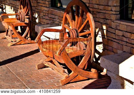 Hand Made Wagon Wheel Made Into A Outdoor Seat On A Front Porch