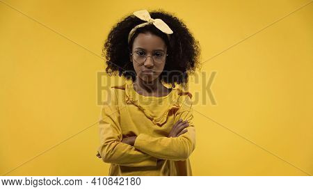 Displeased African American Girl In Glasses Standing With Crossed Arms Isolated On Yellow