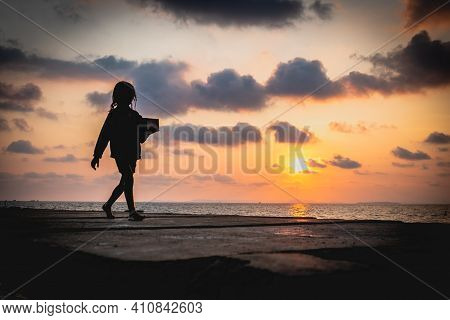 A Young Cambodian Girl Walks Home After A Long Days Work Selling Trinkets To Various Travelers On He