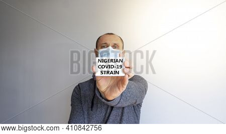 Covid-19 Nigerian Strain Symbol. White Card, Words 'nigerian Strain'. A Young Man In A Grey Wear And