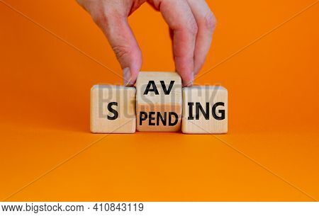 Saving Or Spending Symbol. Businessman Turns Cubes And Changes The Word 'spending' To 'saving'. Beau