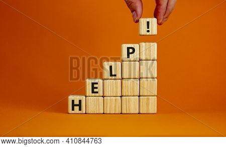 Support And Help Symbol. Pyramid From Wooden Cubes With The Word 'help'. Businessman Hand. Business,