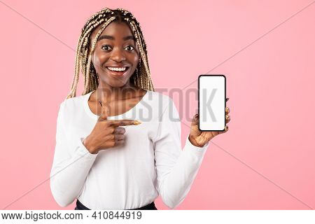 Positive Young African American Lady Showing Modern Smartphone, Pointing At Empty Screen, Recommendi