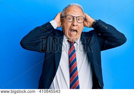Senior caucasian man wearing business suit and tie crazy and scared with hands on head, afraid and surprised of shock with open mouth