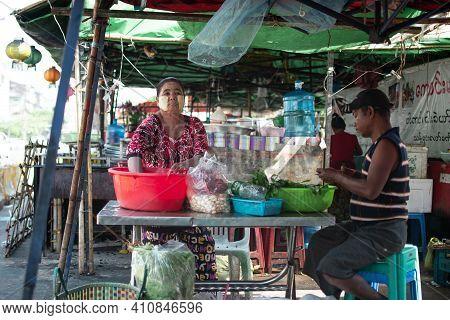 Yangon, Myanmar - January 1 2020: A Local Burmese Woman In Traditional Longyi And Thanaka Prepares V