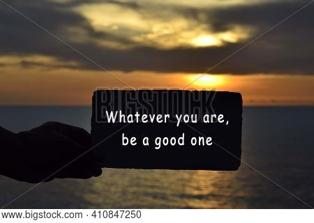 Whatever You Are Be A Good One Text On Hand Holding Torn Paper With Blurred Background Of Sunset At