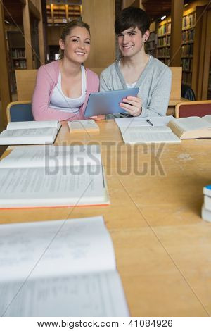 Smiling students with tablet pc at study table in college library