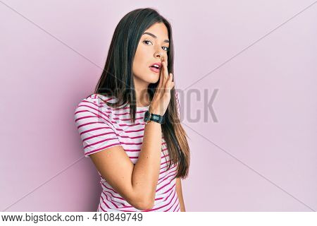 Young brunette woman wearing casual clothes over pink background hand on mouth telling secret rumor, whispering malicious talk conversation