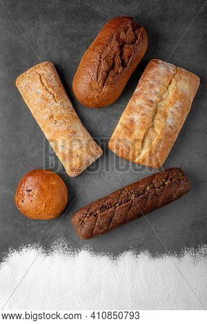 Baking Dark Background With Several Different Fresh Baked Whole Loaves Of Bread Top View On Gray Sur