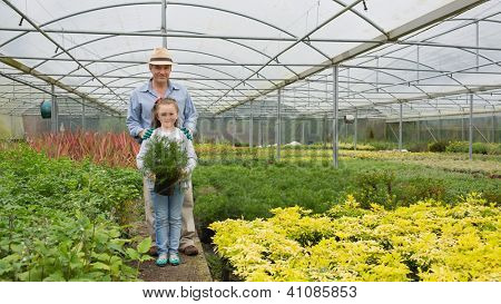 Gardener and grandddaughter in the greenhouse holding large potted plant