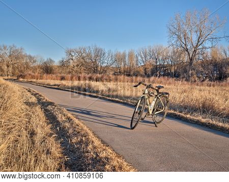 touring bicycle in late fall or winter scenery in sunset light on a bike trail in northern Colorado, recreation and commuting concept