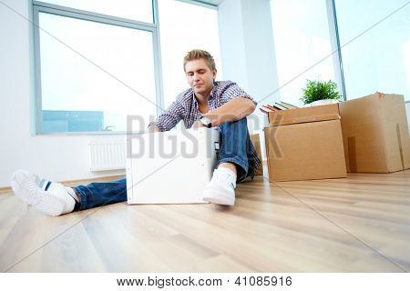 A young guy sitting on the floor of new house and unpacking box