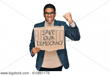 Young handsome hispanic man holding save our democracy protest banner annoyed and frustrated shouting with anger, yelling crazy with anger and hand raised