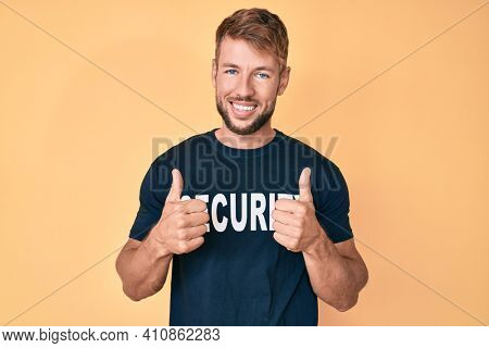 Young caucasian man wearing security t shirt success sign doing positive gesture with hand, thumbs up smiling and happy. cheerful expression and winner gesture.