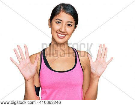 Beautiful asian young sport woman wearing sportswear and arm band showing and pointing up with fingers number ten while smiling confident and happy.