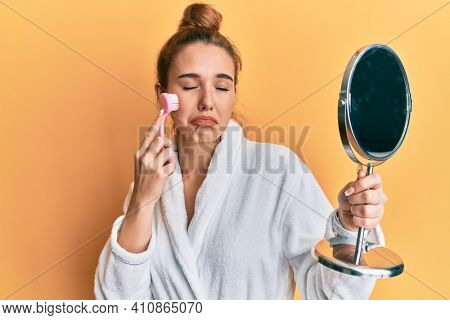 Young blonde woman wearing robe holding makeup remover brush depressed and worry for distress, crying angry and afraid. sad expression.
