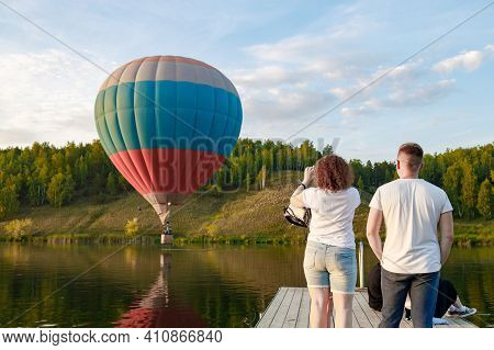 People Take Pictures Of The Landed Balloon In The River, Tourists On The River Bank