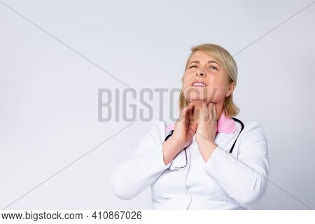 Sick Mid-aged Female Doctor Complaining About Sore Throat On White Background With Plenty Side For M
