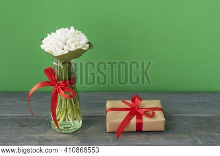 White Snowdrops In Vase And Wrapped Giftbox Tired Up With Red Ribbon On Green And Wooden Background,