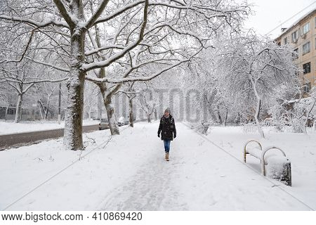 Young Woman Walking Alone At Empty Snow-covered Winter Street. Snowy Winter.