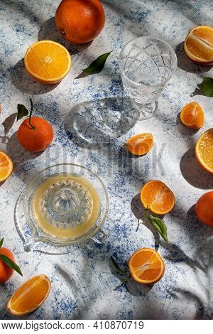 Modern Trend Flat Lay With Hard Shadows, Oranges And Clementines Vitamin Juice On Light Blue Table