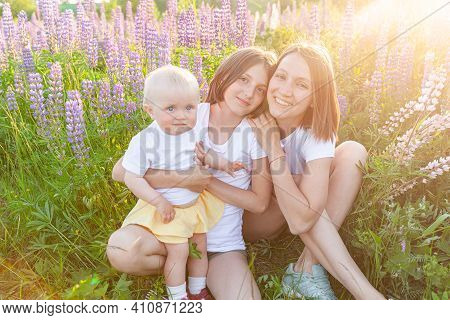 Young Mother Embracing Her Kids Outdoor. Woman Baby Child And Teenage Girl Sitting On Summer Field W