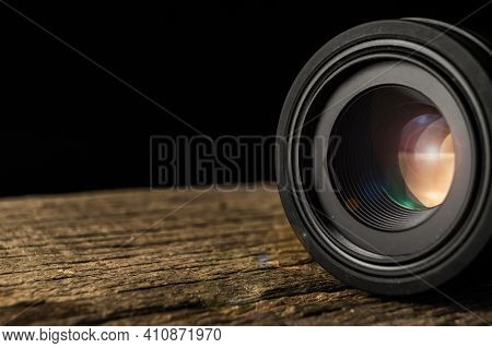 Black Camera Lense On The Wooden Table With Dark Background.