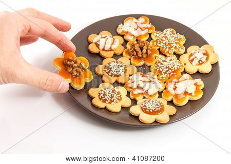 Hand Taking A Homemade Butter Cookie With Caramel And Walnut From A Plate With Cookies