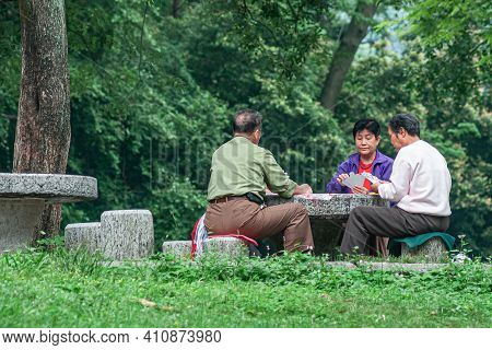 Guilin, China - May 11, 2010: Seven Star Park. Woman And 2 Men Play Cards On Stone Table Surrounded