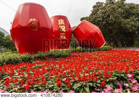 Guilin, China - May 11, 2010: Seven Star Park. Giant Red Drums Statue Set In Red And Pink Flowers At