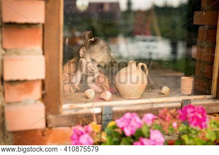 The Girl Sits Alone At Home By The Window. A Child Looks Out Of The Window. Dirty, Unwashed Glass. D