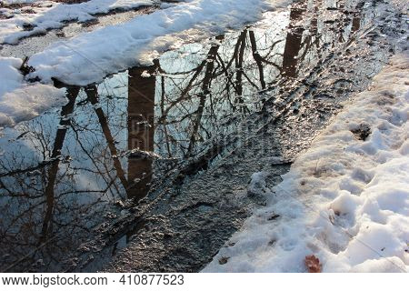 Slush And Mud On Road From Melting Snow On The Road During Spring Thaw. Spring Landscape With Trees