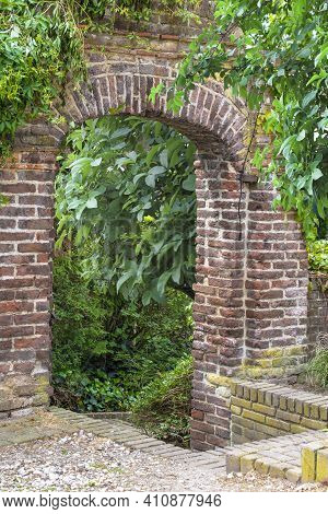 Stone Arch With Leaves. The Ancient Stone Arch Was Overgrown With Greenery. Concept Of Human Life Wi