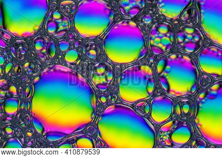 Top View Of Bright Rainbow Texture Of Soap Foam. Abstract Vibrant Colorful Background Of Soapy Lathe