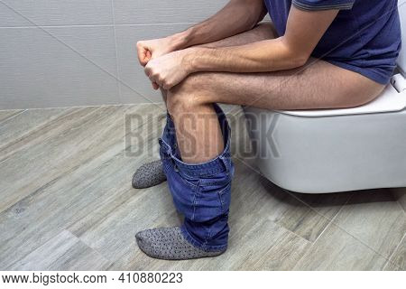 Closeup View Of Man Suffering From Hemorrhoid On Toilet Bowl In Rest Room