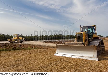 Road Roller And Bulldozer On The Construction Of A New Road. Construction Machinery. Dedicated Const