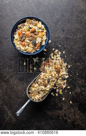 Beakfast cereals in bowl. Healthy muesli with oat flakes, nuts and raisins on black table. Top view.