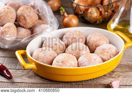 Frozen Meatballs In A Baking Dish On A Wooden Table, Ready To Eat
