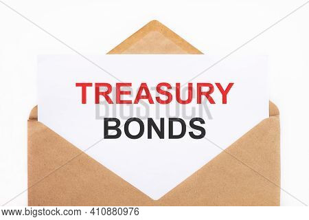 A White Sheet With The Text Treasury Bonds Lies In An Open Craft Envelope On A White Background With