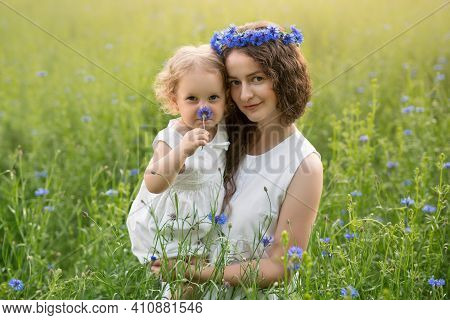 Mother And Daughter In A Field Of Cornflowers. Wreaths Of Cornflowers On The Head Of A Woman And A G