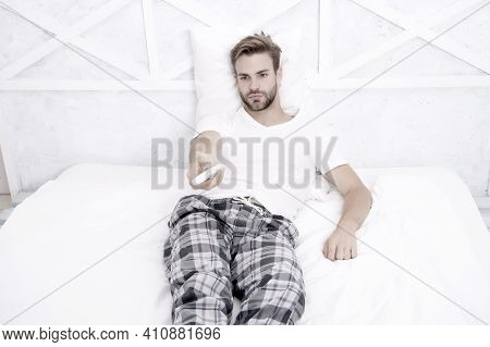 Best Alternatives To Cable Tv. Handsome Man In Pajamas With Remote Control. Guy Watching Television