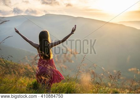 Rear View Of A Happy Woman Hiker In Red Dress Standing On Grassy Hill On A Windy Evening In Autumn M