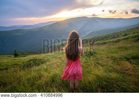 Young Woman In Red Dress Walking On Grass Field On A Windy Evening In Autumn Mountains.