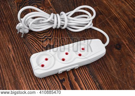 White Extension. Electrical Power White Strip Or Extension Block With Sockets On Wood Background. St
