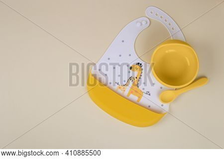Baby Accessories On Light Yellow Background, Flat Lay. Composition With Space For Text. Baby Bib And