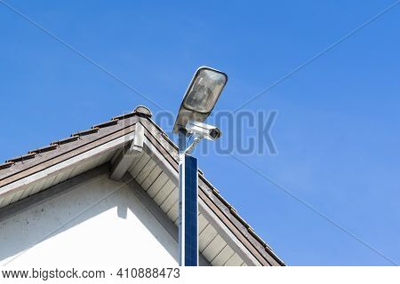 White Solar Powered Surveillance Camera In Front Of A House Facade, Constant Surveillance Is A Growi