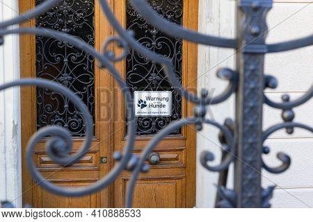 Lattice Door In Foreground, Brown Wooden Door In Background With German Text Sign, German Text Trans