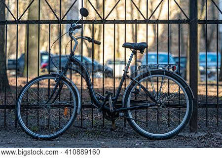 Vintage City Bicycle Parken Against A Metal Fence On A Sunny Day